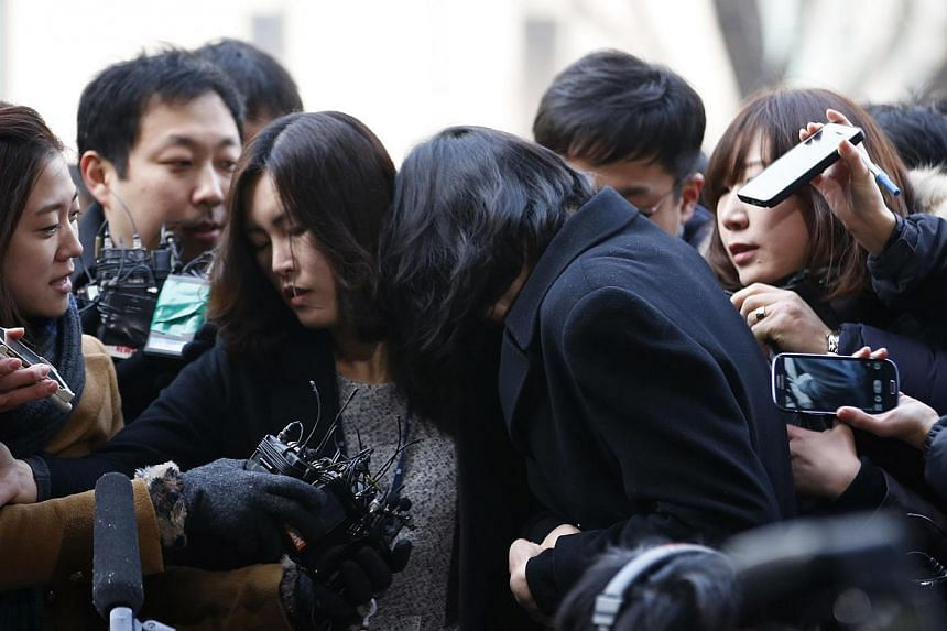 Cho Hyun Ah (centre, with her back to the camera), also known as Heather Cho, daughter Korean Air Lines chairman Cho Yang Ho, arriving to attend a hearing for reviewing the prosecution's detention warrant request against her, at the Seoul Western Dis