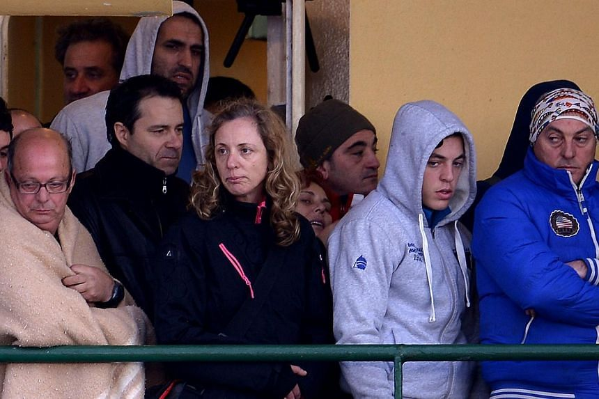 Passengers among 49 survivors evacuated from the burning ferry Norman Atlantic waiting to disembark from the Singapore-flagged cargo container ship Spirit of Piraeus as they arrive in the harbour of Bari, southern Italy, on Dec 29, 2014. -- PHOTO: AF