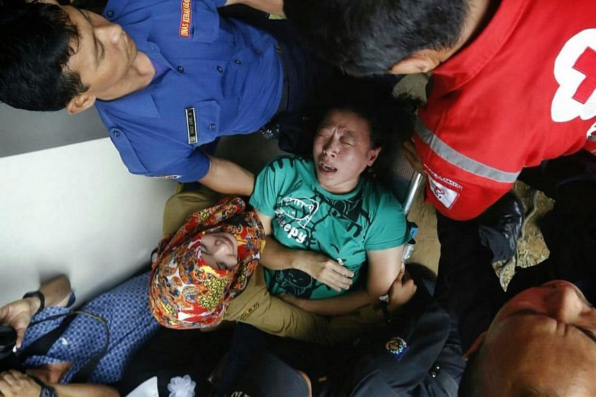 A family member being carried out of the crisis centre at Juanda International Airport Terminal 2 in Surabaya after watching first footages of a dead body found on Dec 30, 2014. -- ST PHOTO: KEVIN LIM
