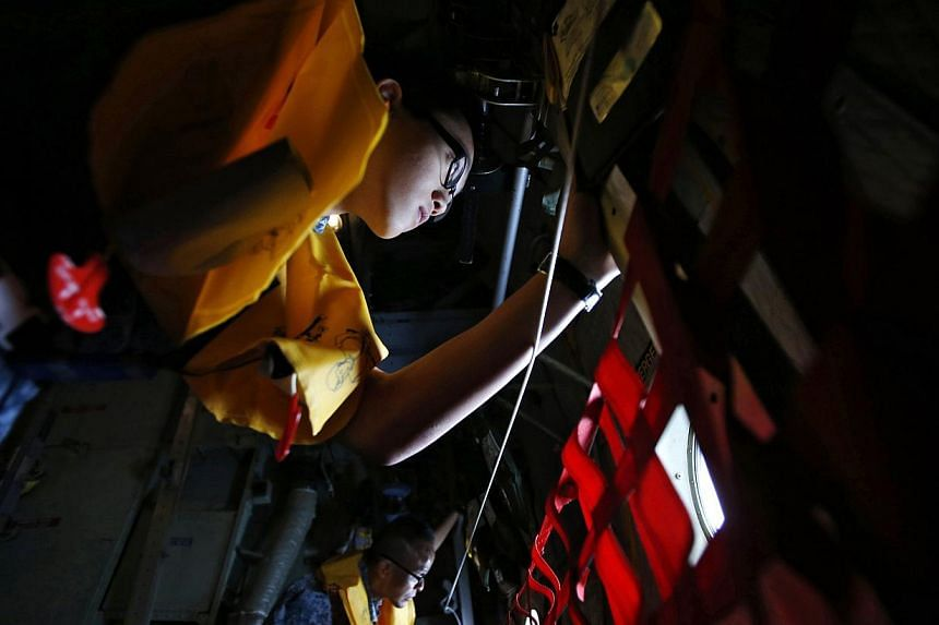 Republic of Singapore Air Force personnel survey the waters during a search and locate operation for the missing AirAsia QZ8501 plane at an undisclosed search area on Dec 30, 2014. Singapore air accident experts will depart on Wednesday morning to as