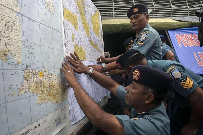 Indonesian Air Force officials show maps to journalists of the search area for the missing Malaysian air carrier AirAsia Flight QZ8501, at the airport in Surabaya, East Java, on Dec 29, 2014.  Indonesia has asked the United States for help