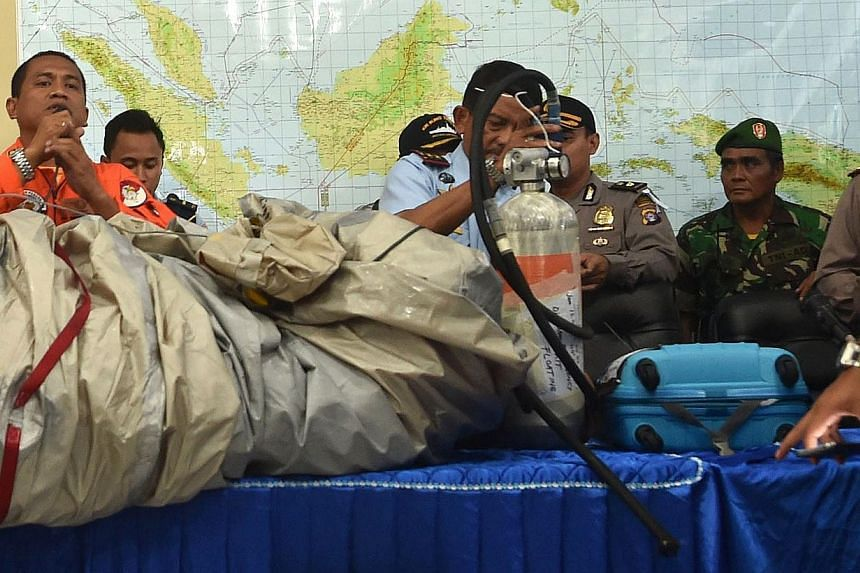 Members of the Indonesian air force show items retrieved from the Java sea during search and rescue operations for the missing AirAsia flight QZ8501, in Pangkalan Bun, Central Kalimantan on December 30, 2014. -- PHOTO: AFP