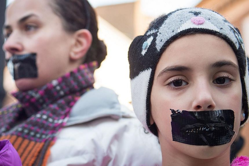 Demonstrators wearing tape over their mouths as they protest outside the Egyptian embassy in central London on Dec 29, 2014, to mark the one year anniversary of the arrest of three Al Jazeera journalists in Egypt. -- PHOTO: AFP