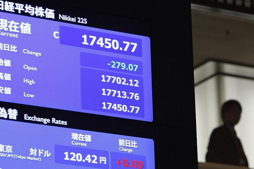 A man stands next to a stock quotation board displaying Japan's Nikkei average at the Tokyo Stock Exchange in Tokyo on Dec 30, 2014. -- PHOTO: REUTERS