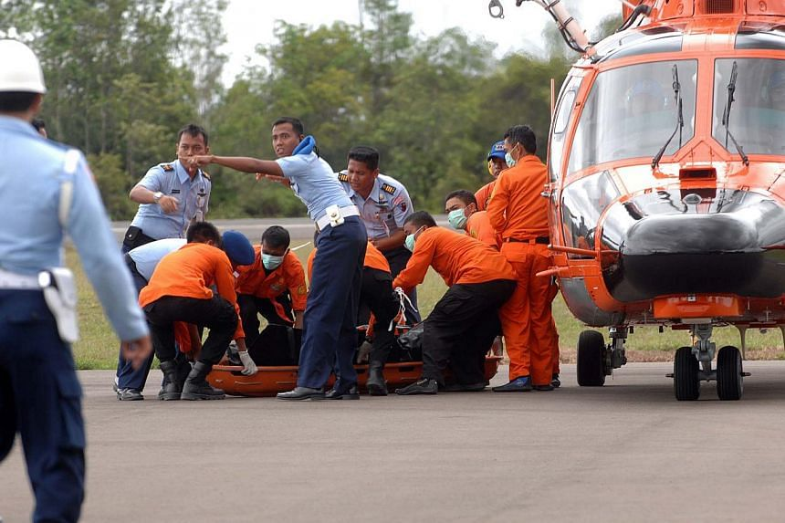 Members of an Indonesian search and rescue team prepare to carry a body on a stretcher during the recovery of victims who were on board the crashed AirAsia flight QZ8501 in Pangkalan Bun on Dec 31, 2014. -- PHOTO: AFP