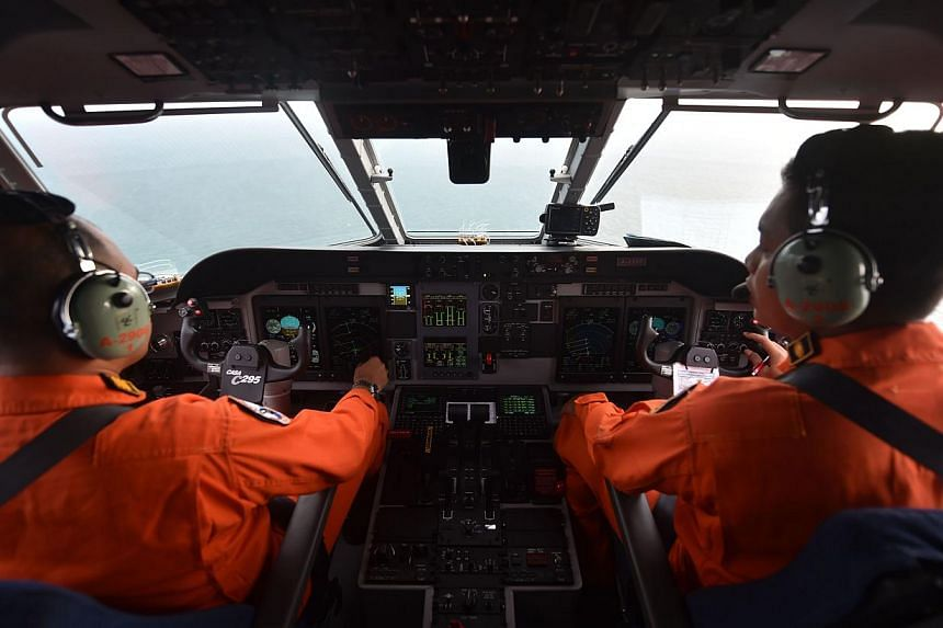 Pilots of the Indonesian air force keeping a look out during search operations for the missing AirAsia flight QZ8501, in Pangkalan Bun, Central Kalimantan on Dec 30, 2014. -- PHOTO: AFP