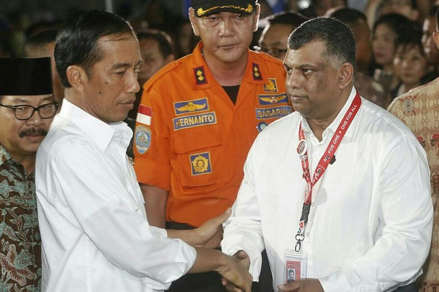 Mr Fernandes (right) greeting Indonesian President Joko Widodo when the latter arrived yesterday at the crisis centre at Juanda International Airport Terminal 2 in Surabaya to meet grieving family members.