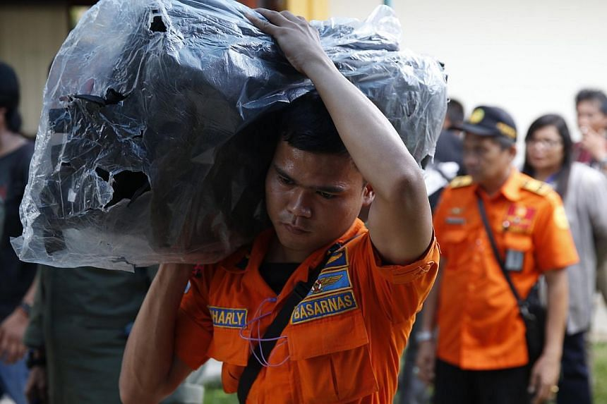A search and rescue worker preparing to load body bags onto a flight to Kalimantan in Pangkal Pinang on Indonesia's Bangka island yesterday. As operations move to search and recovery, it would take weeks before the authorities and investigators are a