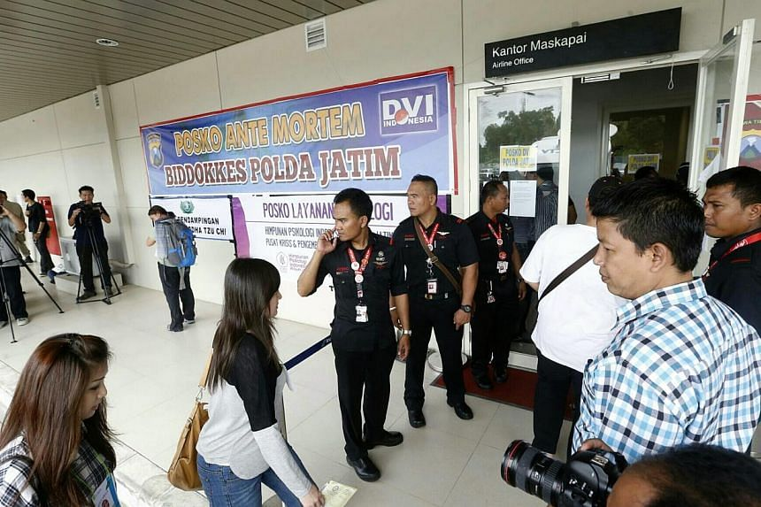 Relatives of passengers onboard AirAsia flight QZ8501 enter a room in the terminal building of Juanda International Airport in Surabaya on Dec 31 to provide DNA samples to assist in the identification of bodies. -- ST PHOTO: KEVIN LIM