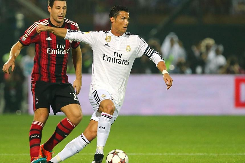 Real Madrid's forward Cristiano Ronaldo (right) vies for the ball against AC Milan's defender Daniele Bonera during their friendly football match on Dec 30, 2014 at the Sevens Stadium in Dubai. -- PHOTO:  AFP