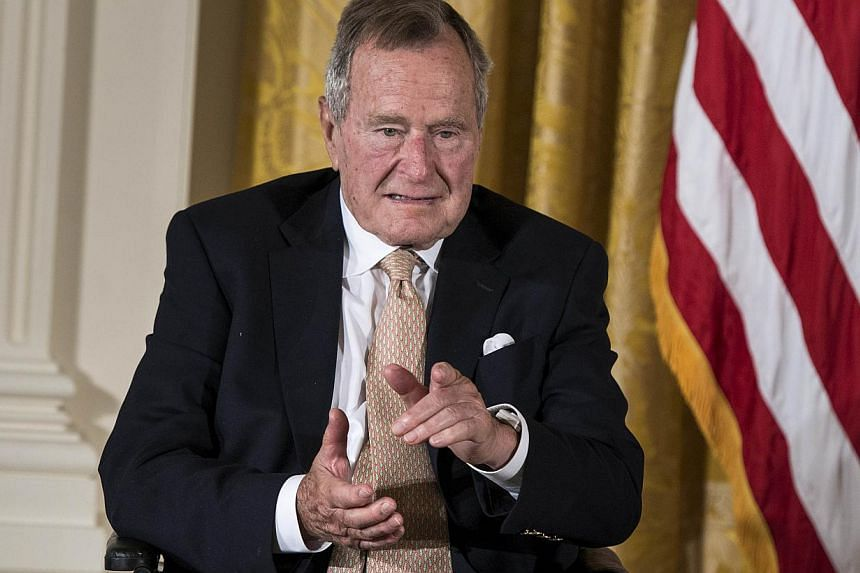 Former US President George H.W. Bush, 90, (above, in a 2013 file photo) was released from a Houston hospital on Tuesday after a week-long stay brought on by breathing difficulties, his spokesman said. -- PHOTO: AFP