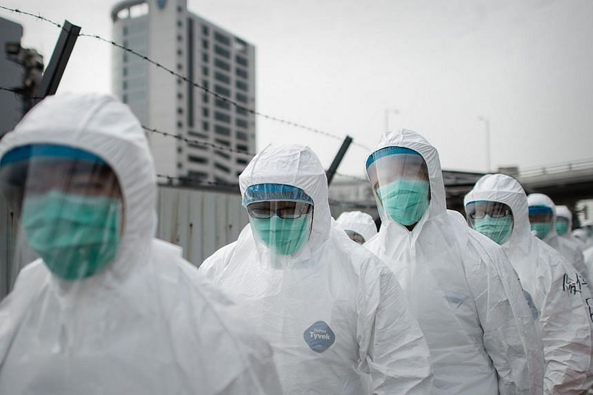 A file picture taken Jan 28, 2014, shows officials wearing masks and protective suits ahead of a mass bird cull in Hong Kong.Hong Kong authorities said Wednesday they will cull 15,000 chickens after the deadly H7N9 virus was discovered in poult