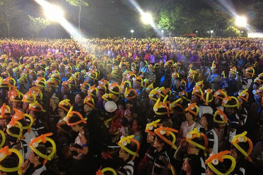 Ang Mo Kio GRC residents gather at the grand lawn at Bishan-Ang Mo Kio park in an attempt to break the world record for most number of people wearing balloon hats with 12,000 balloon hats on Dec 31, 2014, as part of the New Year's Eve celebrations. -
