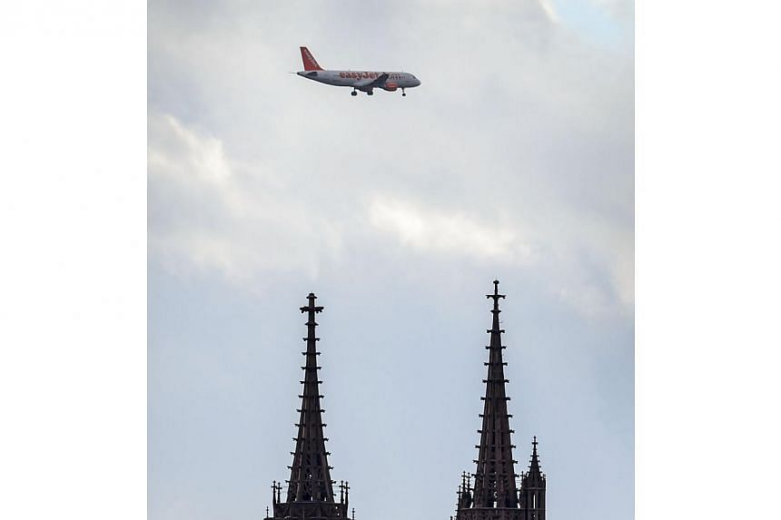 An easyJet plane flies above the cathedral at Basel. British low-cost carrier easyJet scrapped 138 French flights scheduled for New Year's Eve and New Year's Day due to a new round of strikes by cabin crew over profit sharing and staff rotas. --