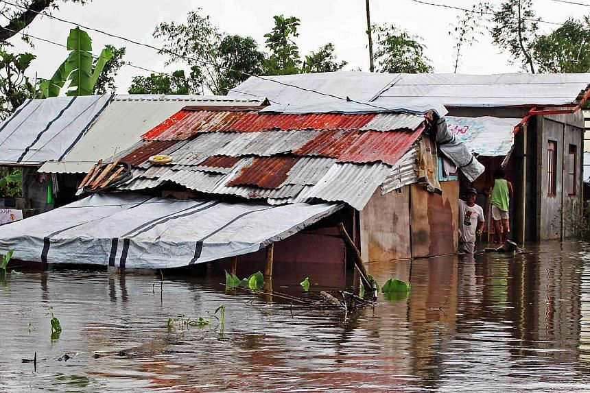 A resident looks out from his home after tropical storm Jangmi caused flooding in Palo town, Samar province, on Dec 30, 2014.The death toll from flooding and landslides in the Philippines wrought by the storm rose to 53 on Dec 31, officials sai