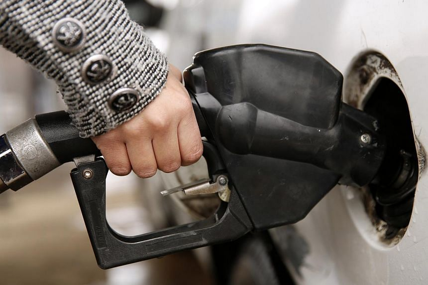 "A woman pumping petrol at a station in Falls Church, Virginia on Dec 16, 2014. The US government has granted permission to ""some"" companies to sell lightly treated condensate abroad. -- PHOTO: REUTERS"
