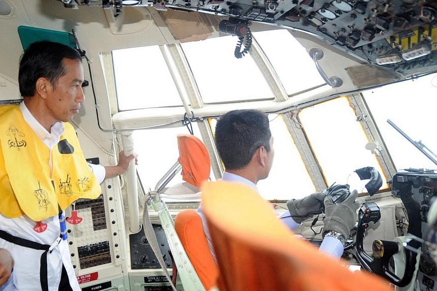 Indonesian President Joko Widodo (left) in the cockpit of an air force Hercules C-130 aircraft during the search and locate operation for missing AirAsia flight QZ8501 on Dec 30, 2014. -- PHOTO: AFP/RUSMAN/PRESIDENTIAL PALACE