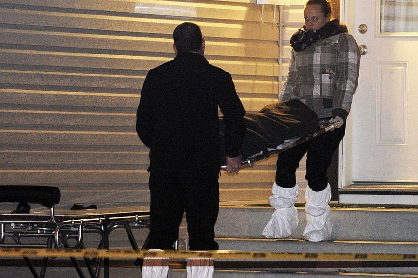Members of the coroner's office removing a body from one of three crime scenes where a total of nine people were found dead in north Edmonton, Alberta, on Dec 30, 2014. -- PHOTO: REUTERS