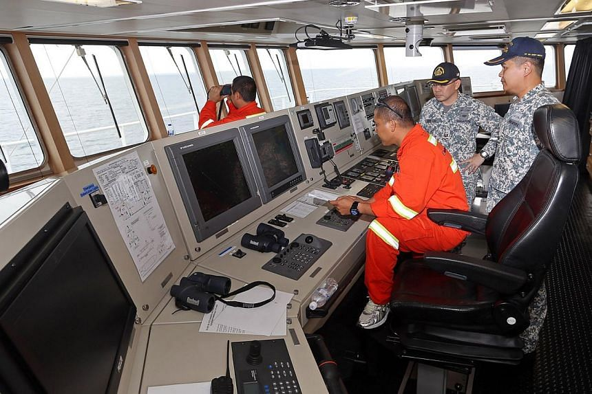 (From right) Major Wee Hong Tat, 33 (Deputy Officer-Commanding), Major John Lau, 42 (Attached Watch Officer), and 2nd Officer Ronald Tecson, 37 (commercial crew), at the bridge of the MV Swift Rescue, the fourth ship to be sent by Singapore to help i