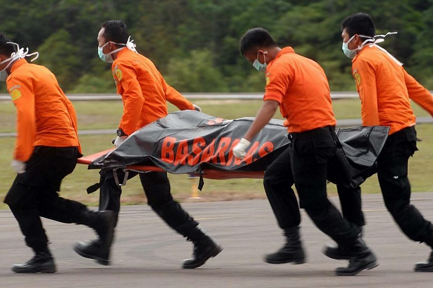 Members of an Indonesian search and rescue team carry a dead body with a stretcher during the recovery of victims who were onboard the crashed AirAsia flight QZ8501 in Pangkalan Bun on Dec 31, 2014. -- PHOTO: AFP