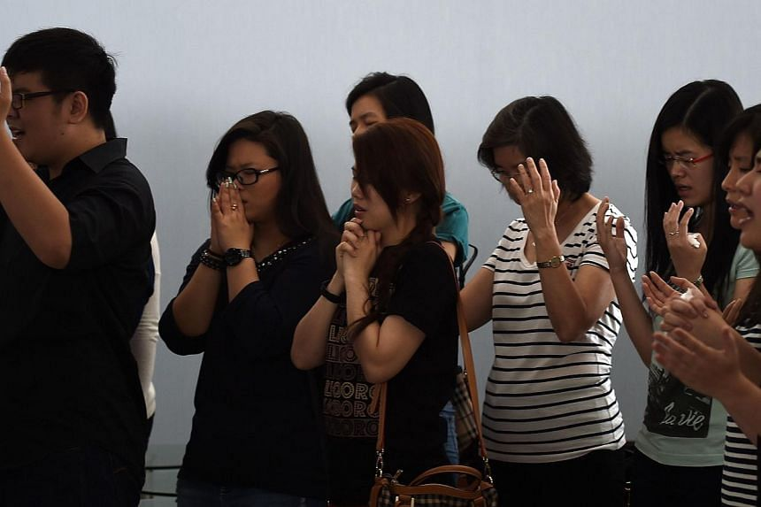 Family members of passengers onboard the plane pray inside a holding room at Juanda International Airport in Surabaya on Dec 31, 2014. -- PHOTO: AFP