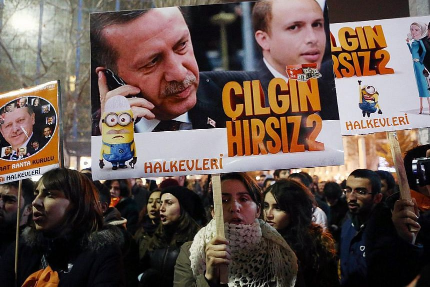 """People hold placards with images of Turkish President Recep Tayyip Erdogan and his son Bilal Erdogan (centre right) that read """"Crazy thief"""" as they protest against corruption in Ankara, on Dec 17, 2014. -- PHOTO: AFP"""