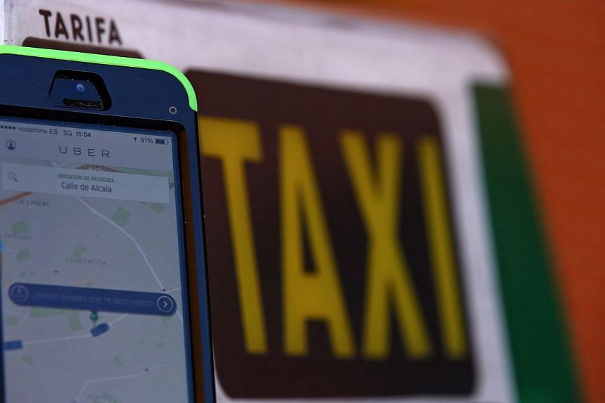 Service app Uber on a smartphone next to a taxi sign is seen in this photo illustration taken in Madrid on Dec 10, 2014. -- PHOTO: REUTERS
