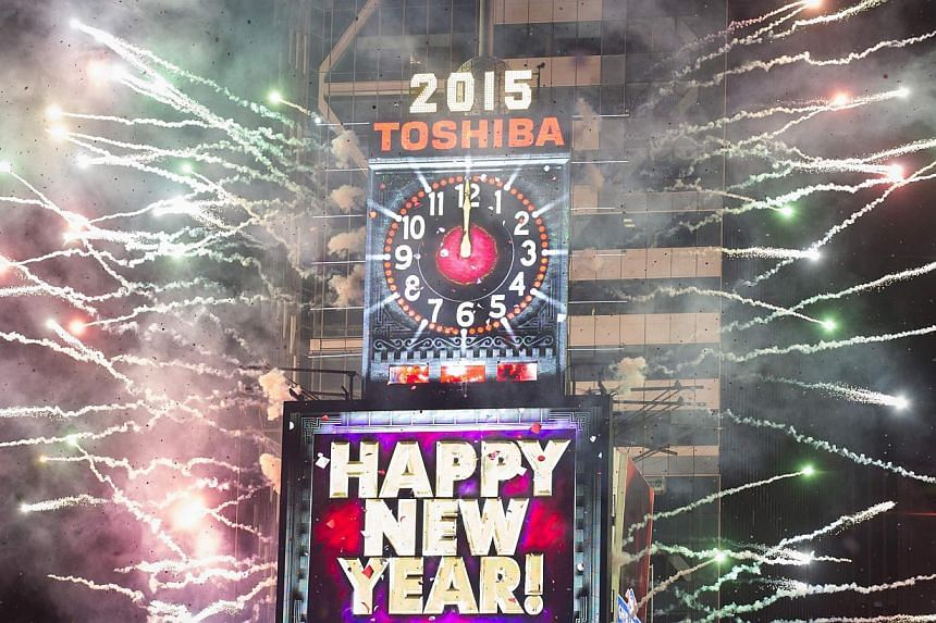 Fireworks go off and confetti fly around the New Year's Eve Ball Drop after the clock strikes midnight during New Year's eve celebrations in Times Square, New York  on Jan 1, 2015. Roughly a million revelers packed New York's Times Square a