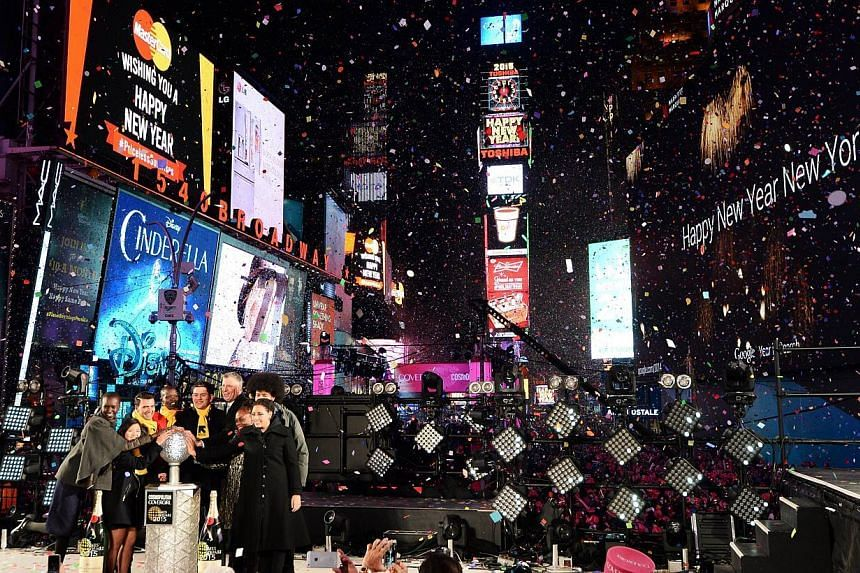 New York City Mayor Bill de Blasio (left, on stage) along with others cheer as the ball drops at the flagpole atop of One Times Square in New York on Jan 1, 2015. -- PHOTO: AFP
