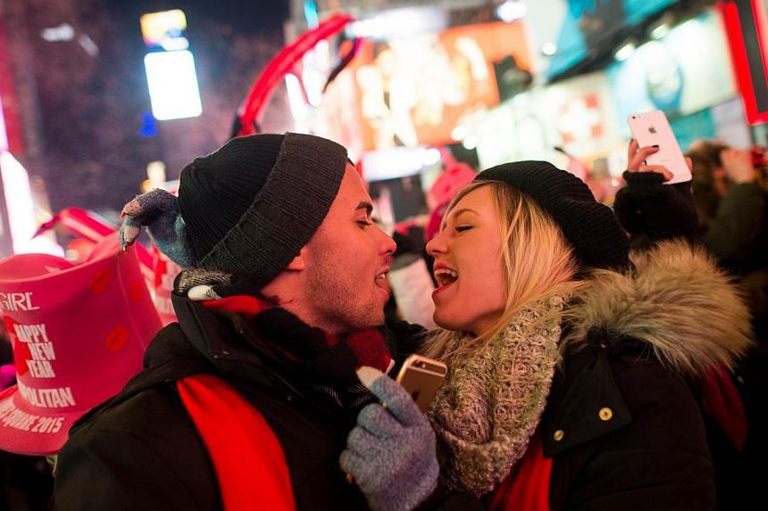 Rhea Coulson, 20, and Angel Garcia (left) from Florida kiss at midnight as they celebrate the new year in Times Square on Jan 1, 2015, in New York City. -- PHOTO: AFP