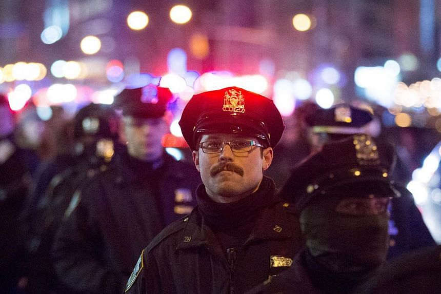 Police watch over a protest march against police brutality that traveled from Union Square to Times Square on Dec 31, 2014, in New York City. -- PHOTO: AFP