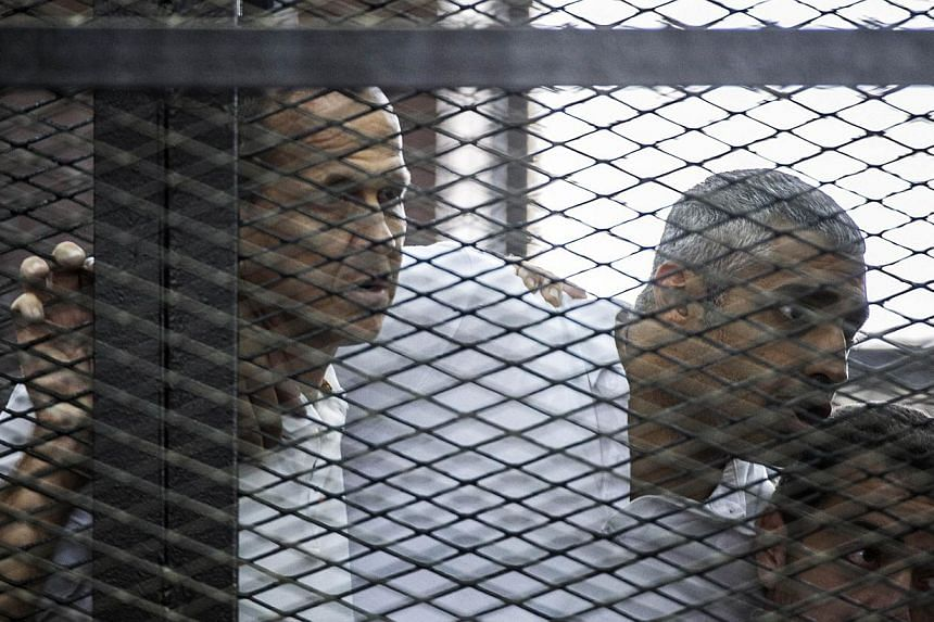 Al-Jazeera journalists Peter Greste (left), Mohamed Fadel Fahmy (centre) and Baher Mohamed listening to the verdict inside the defendants cage during their trial for allegedly supporting the Muslim Brotherhood,at the police institute near Cairo