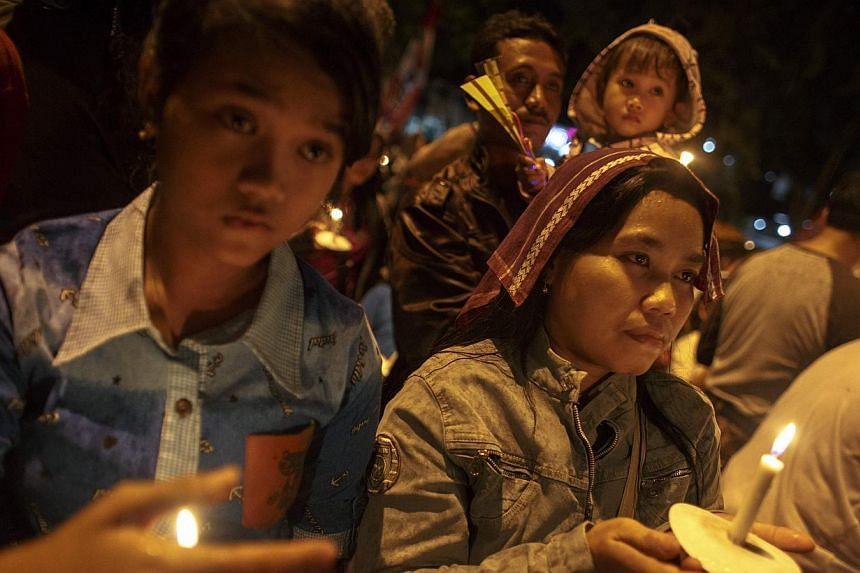 Indonesians hold up candles during a candle light vigil for the victims of AirAsia flight QZ8501 at Surabaya Dec 31, 2014. -- PHOTO: REUTERS