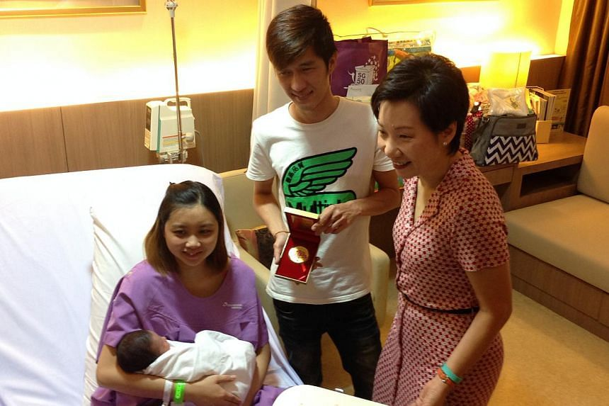 Ms Grace Fu, Minister in the Prime Minister's Office, presented the parents with the first SG50 Baby Jubilee Gift at Thomson Medical Centre on Thursday morning. -- ST PHOTO: YEO SAM JO