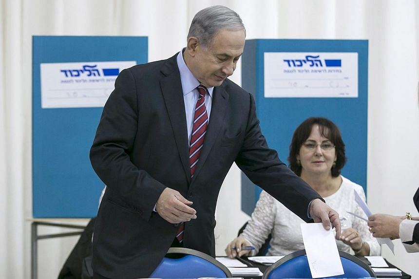 Israel's Prime Minister Benjamin Netanyahu (left) and his wife Sara (just seen, far right) cast their ballots for the Likud primary at a polling station in Jerusalem Dec 31, 2014. -- PHOTO: REUTERS