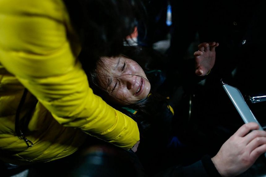 A family member (centre) cries on a bench at a hospital where some of the victims of a stampede by new year's revellers were sent in Shanghai on Jan 1, 2015. -- PHOTO: AFP