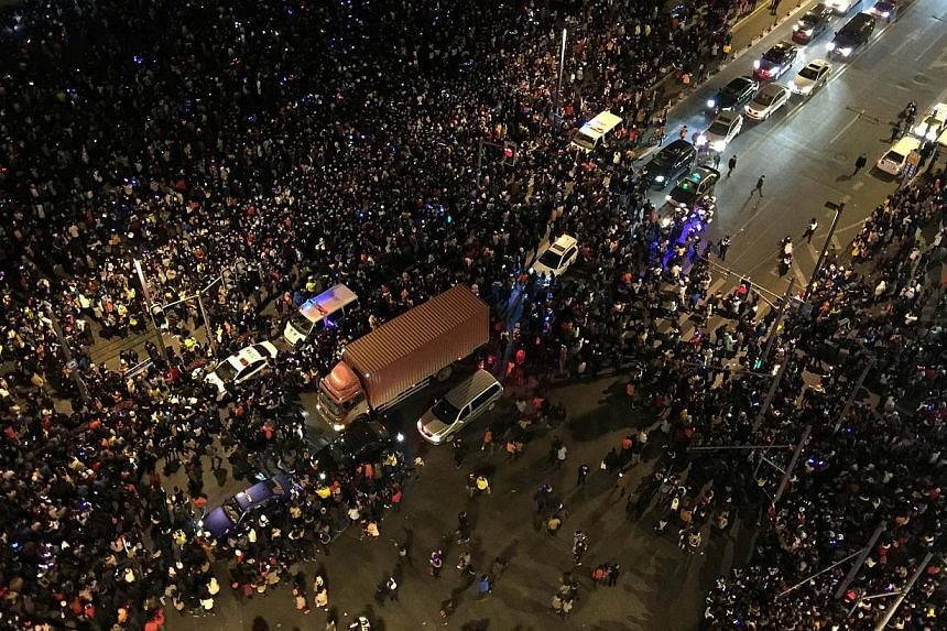 An overhead view showing emergency vehicles (centre) amongst the crowd after a stampede by new year's revellers in Shanghai's historic riverfront in Shanghai on Jan 1, 2015. -- PHOTO: AFP