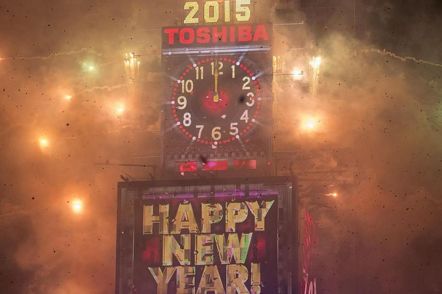Fireworks go off and confetti flies around the New Year's Eve Ball Drop after the clock strikes midnight during New Year's Eve celebrations in Times Square, New York on Jan 1, 2015. -- PHOTO: REUTERS