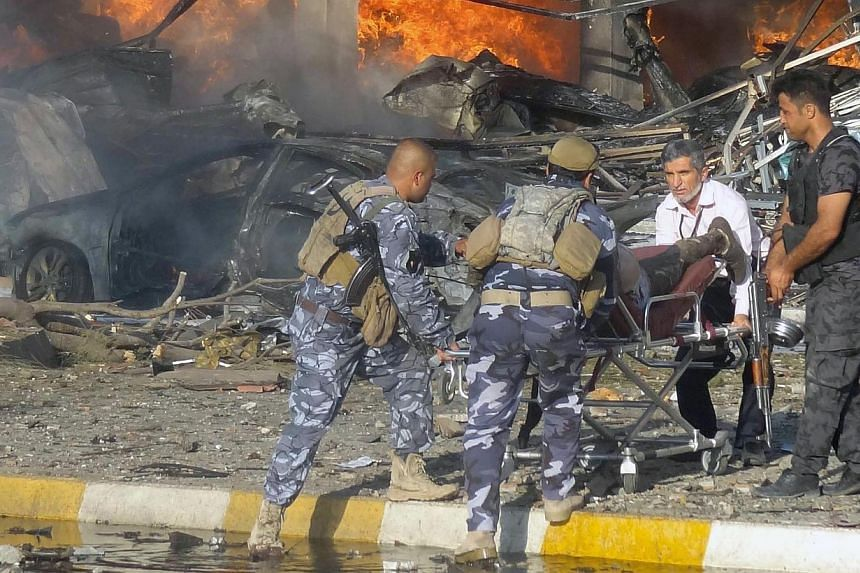 A picture taken Aug 23, 2014 shows Iraqi emergency service personnel wheeling a body at the site of a roadside bomb attack near under-construction buildings in the Kurdish-controlled northern Iraqi city of Kirkuk. Violence in Iraq killed more than 15
