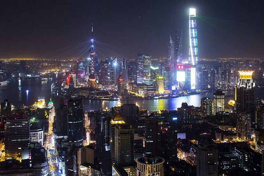 Light and laser illuminate the Lujiazui financial district of Pudong in Shanghai during a light show as part of a New Year countdown celebration on the Bund in Shanghai on Jan 1, 2015. -- PHOTO: REUTERS