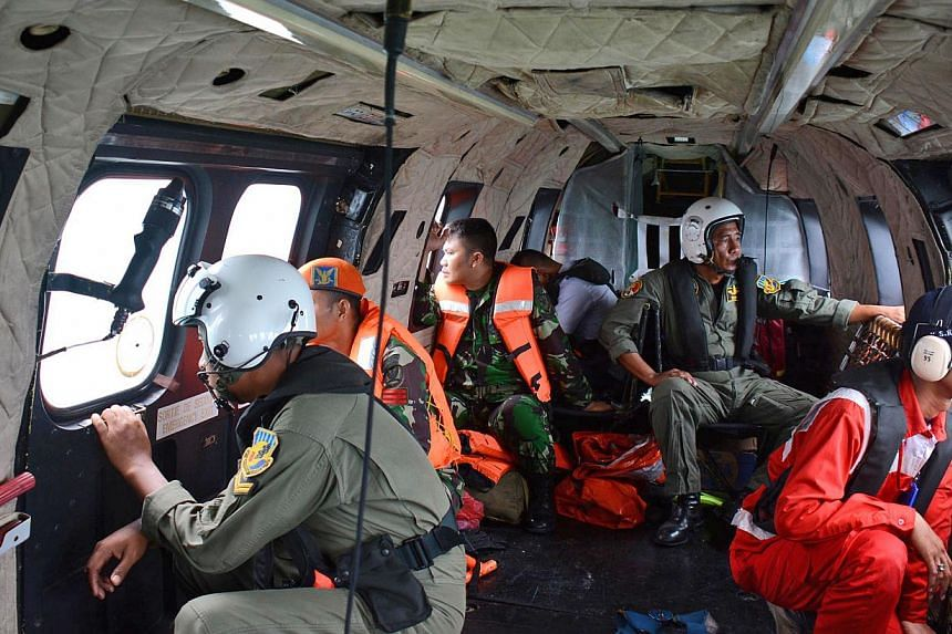 Crewmembers of an Indonesian Air Force Super Puma helicopter of the 6th Air Squadron look out the windows during search operations for victims of AirAsia Flight QZ 8501 over the Java Sea on Jan 1, 2015. -- PHOTO: AFP