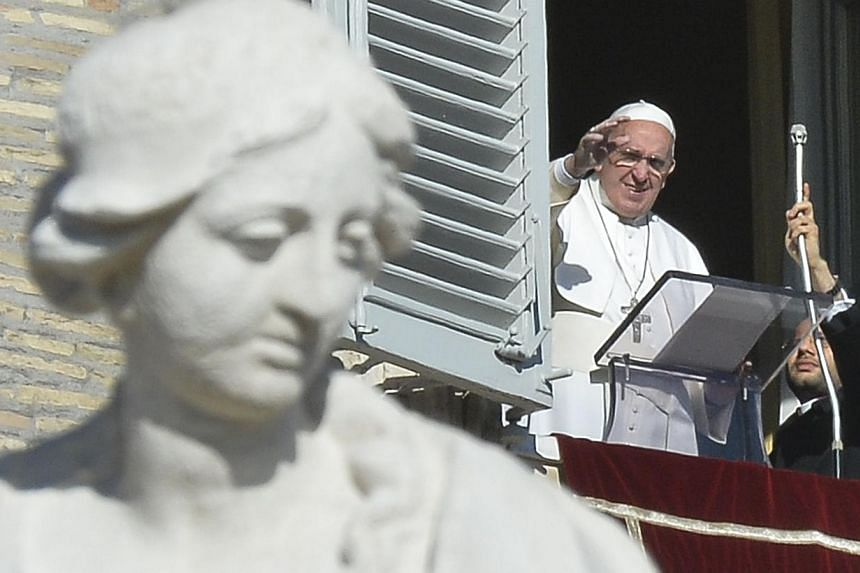 Pope Francis greeting the crowd from the window of the Apostolic Palace overlooking St.Peter's Square during his Angelus prayer on Jan 1, 2015 at the Vatican. -- PHOTO: AFP