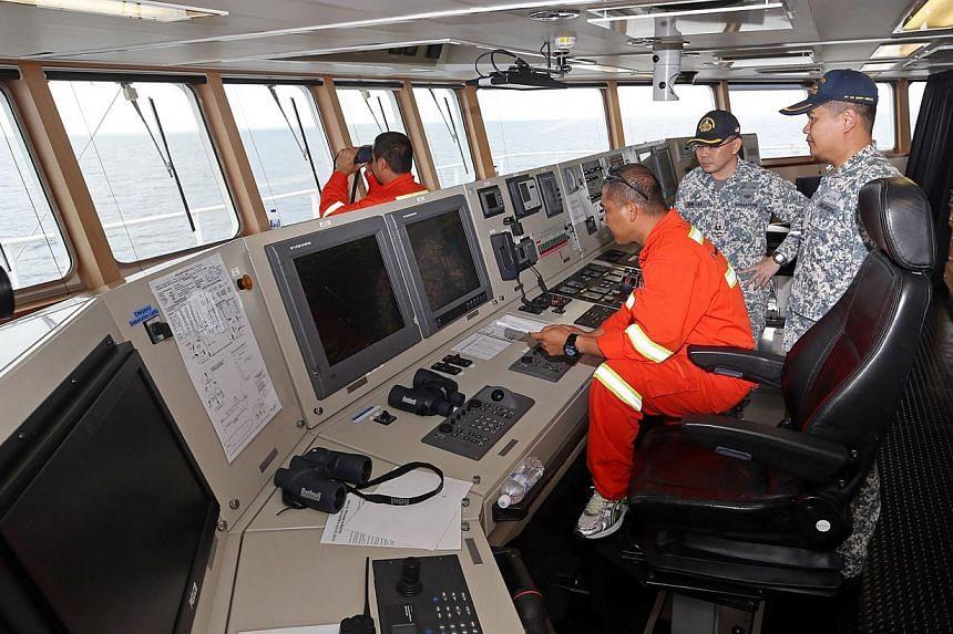 Major Wee Hong Tat, Major John Lau and 2nd Officer Ronald Tecson at the bridge of the MV Swift Rescue. -- ST PHOTO:SEAH KWANG PENG