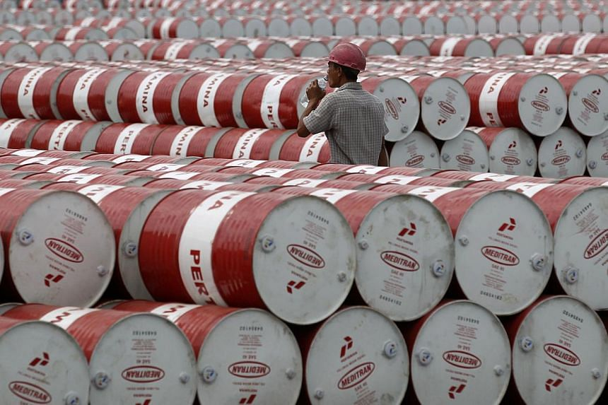 A worker walks in between oil barrels at Pertamina's storage depot in Jakarta in this Jan 26, 2011 photo. -- PHOTO: REUTERS