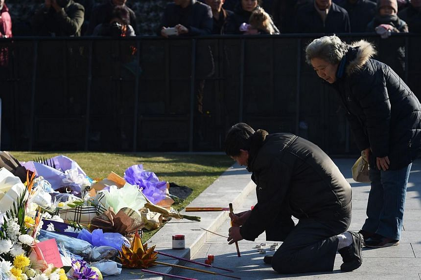 A couple burning incense on Jan 2, 2015,at the site of a New Year's Eve stampede at the Bund in Shanghai. -- PHOTO: AFP