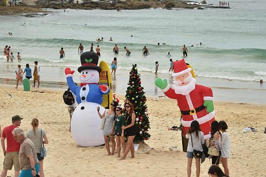 Visitors on Bondi Beach in Sydney on Christmas Day. Swimmers were ordered out of the water and the beach was closed briefly on Jan 2, 2015, after a shark was spotted. -- PHOTO: AFP