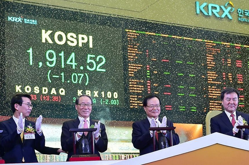South Korea's Financial Services Commission chairman Shin Je Yoon (right) and officers marking the opening of the stock market in the new year at the Korea Exchange in Seoul on Jan 2, 2015. -- PHOTO: AFP