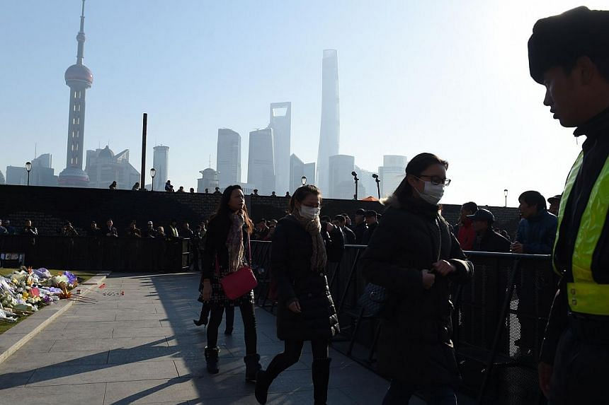 Three mourners walk past a security guard (R) after placing flowers at the site of the New Year's Eve stampede at the Bund in Shanghai on Jan 2, 2015.Dozens of deaths from a crush in Shanghai highlight China's enduring vulnerabilities even as t