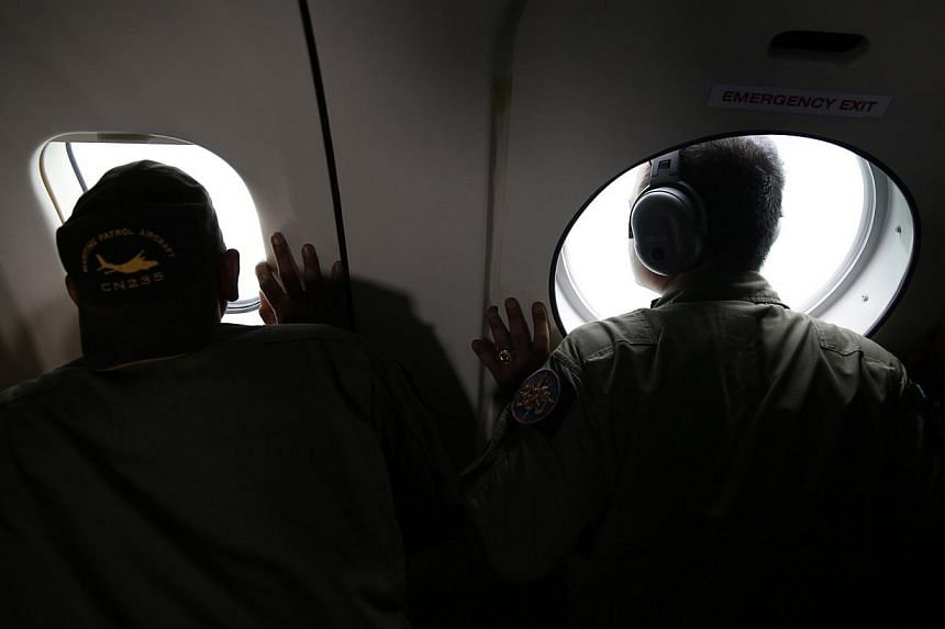 Crew members of an Indonesian Navy maritime surveillance plane look out windows during a search for wreckage and the remains of passengers onboard the AirAsia QZ8501 flight, over the Karimata Strait south of Pangkalan Bun, Central Kalimantan on Jan 1