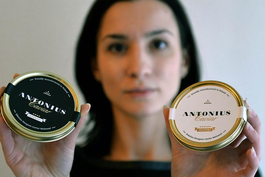 Ms Agata Lakomiak-Winnicka, marketing and sales manager for Antonius caviar, showing two cans of the Polish product on Dec 20, 2014 in Rus, northern Poland. -- PHOTO: AFP